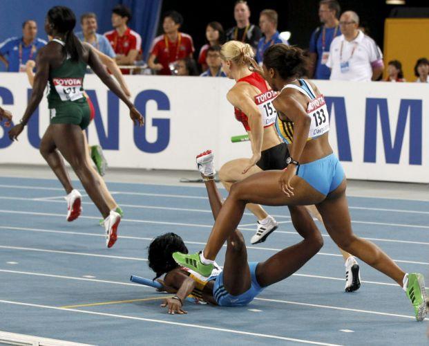 Nivea Smith, de Bahamas, cai na pista sobre a companheira Anthonique Strachan durante eliminatória do revezamento 4x100 m