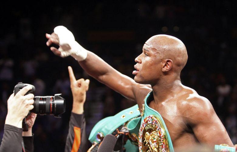 Já com o cinturão dos meio-médios, conquistado contra Victor Ortiz, Floyd Mayweather acena para a torcida no ginásio em Las Vegas, nos Estados Unidos.