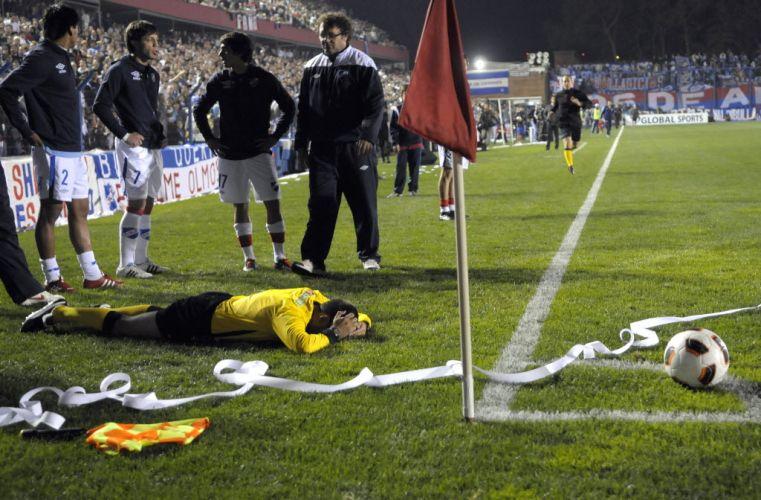 Assistente fica no gramado, após ser atingido por um rolo de papel; partida entre o Nacional, do Uruguai, e o Universidad do Chile, em Montevidéu, foi suspensa