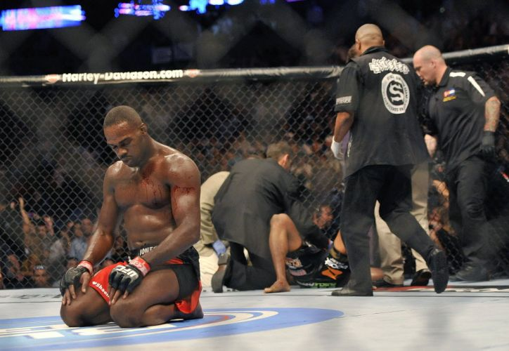 Jon Jones se ajoelha no octgono aps conseguir um mata-leo em Rampage e defender pela primeira vez o cinturo dos meio-pesados