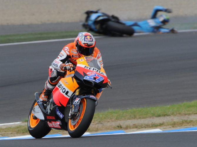 Enquanto australiano Casey Stoner faz a curva, espanhol Alvaro Bautista (ao fundo, de azul) sofre queda na etapa japonesa da MotoGP.