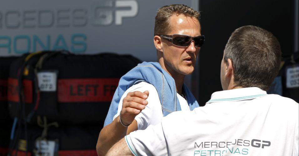 Depois de uma volta rápida de bicicleta pelo circuito de Suzuka, no Japão, o piloto Michael Schumacher conversa com um integrante da Mercedes