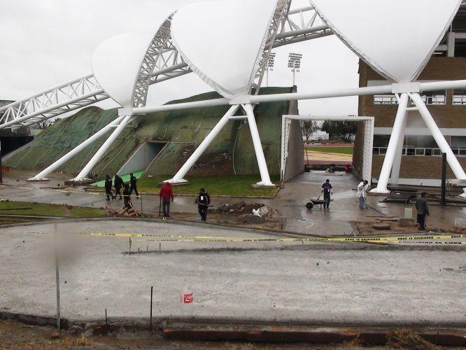 Ferramentas, cimento fresco e operários compõem o cenário do estádio de atletismo do Pan