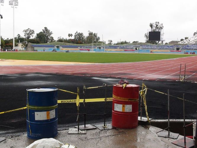 Latões improvisados são usados para limitar o acesso das pessoas à pista de atletismo do estádio Telmex