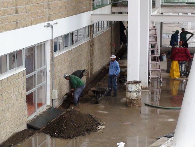 Terra é separada para a jardinagem do estádio, atrapalhada pela chuva causada pela proximidade do furacão Jova
