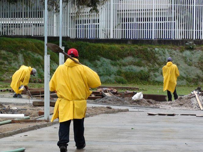 Trabalhadores usam capas de chuva e trabalham no dia da festa pela Virgem de Zapopan para compensar o atraso nas obras do estádio do atletismo