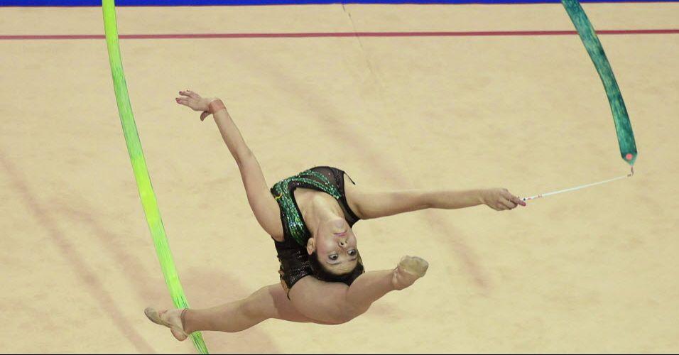Colombiana Carolina Velez encosta a cabeça na parte de trás da coxa, em movimento de sua prova no individual geral
