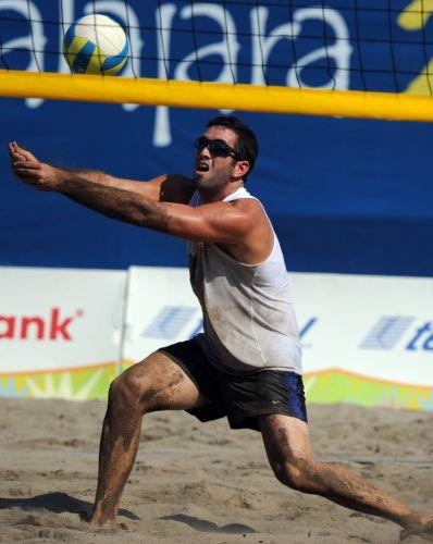 Cristopher Underwood, de Porto Rico, faz recepção na areia úmida durante partida contra a dupla da Jamaica no Pan