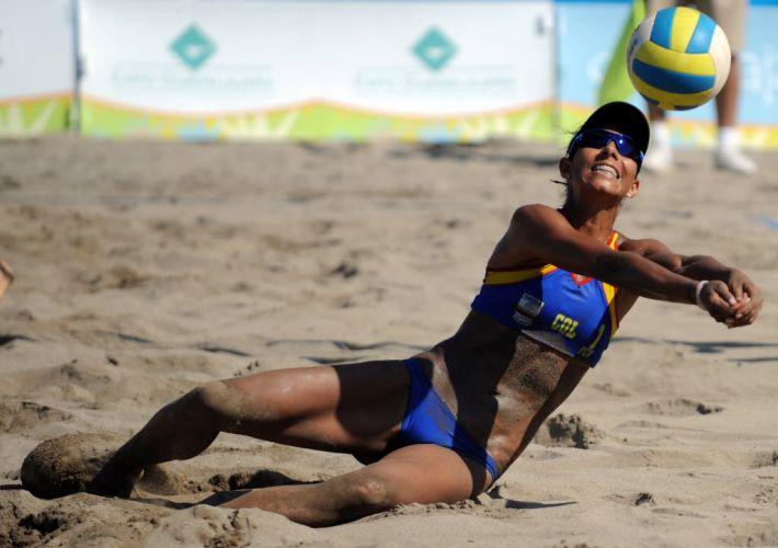 Andrea Galindo, da Colômbia, mergulha para fazer defesa na partida contra dupla americana e se suja ainda mais com a areia-lama do México