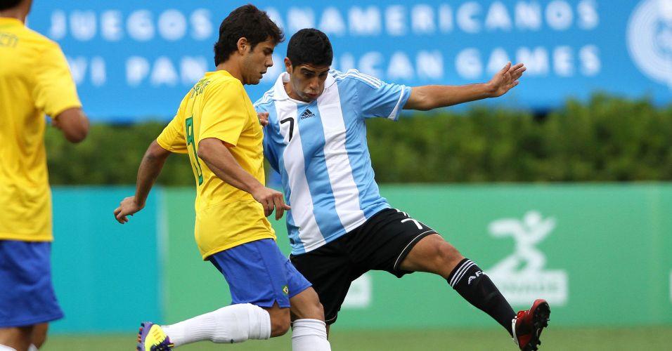 Henrique Almeida toca a bola enquanto recebe a marcação de Matias Laba no clássico entre Brasil e Argentina