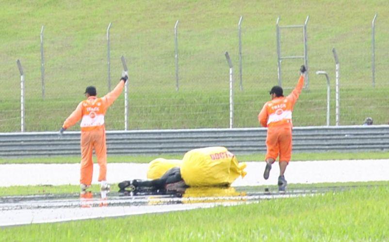 Fiscais pedem ajuda no atendimento ao piloto Marco Simoncelli. Italiano sofreu gravíssimo acidente no início do GP da Malásia de MotoGP. Ele foi levado a um hospital, mas não resistiu aos ferimentos e morreu (23/10/2011)