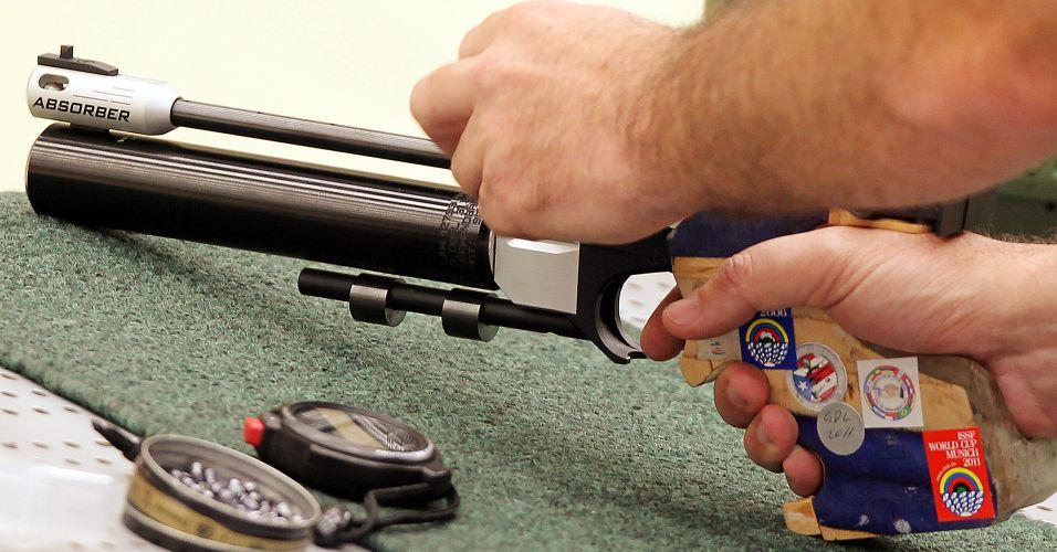 Julio prepara sua arma para mais uma bateria de disparos na final do tiro esportivo