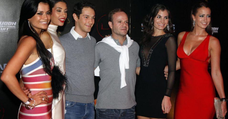 Usando camisas da mesma cor, Bruno Senna e Rubens Barrichello posam ao lado de modelos durante a festa promovida pela organização do GP da Índia após a corrida