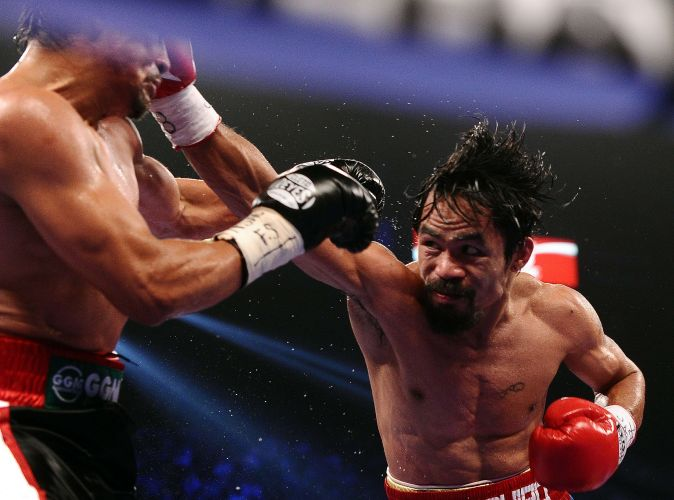 Manny Pacquiao acerta golpe no rosto de Juan Manuel Mrquez. Em deciso polmica dos juzes, filipino derrotou mexicano e foi vaiado pelo pblico em Las Vegas