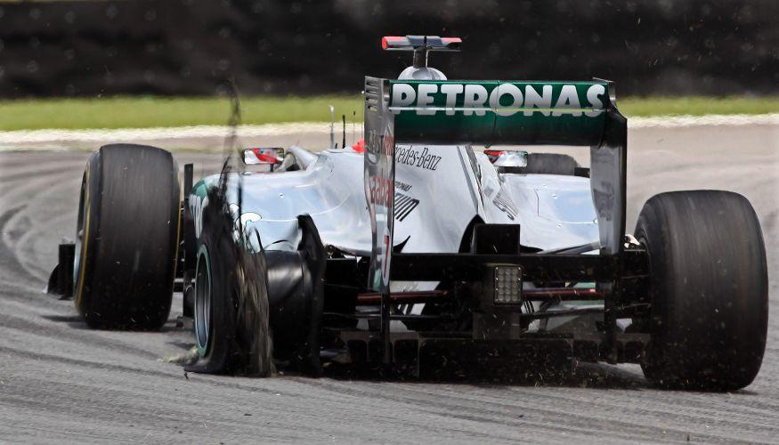 Michael Schumacher tenta levar sua Mercedes para os boxes após ter seu pneu furado em toque com Bruno Senna. Piloto da Renault foi considerado culpado por incidemte e acabou punido com um drive through (passagem pelos boxes)