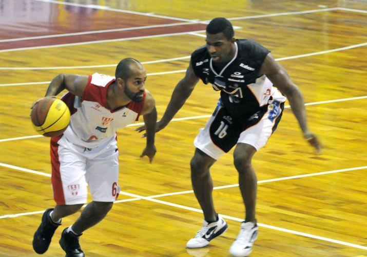 Arnaldinho tenta passar pela marcação na partida entre Tijuca e Bauru