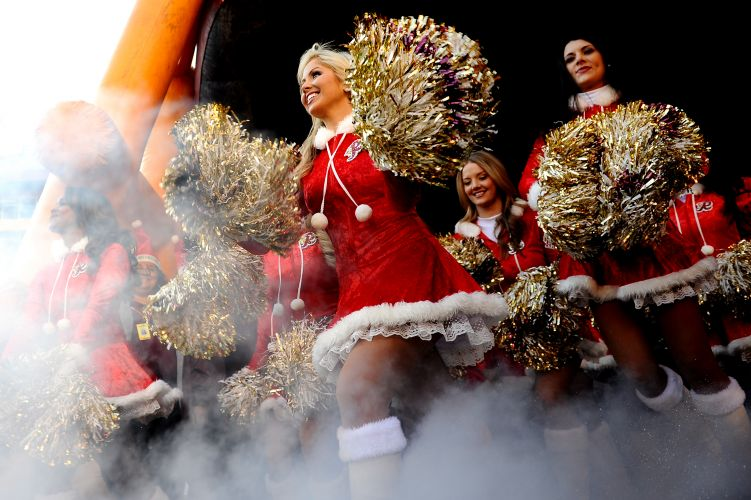 Grupo de cheerleaders do Washington Redskins no momento da entrada no gramado para o jogo contra o Minnesota Vikings. Natal mudou a vestimenta das meninas, que nem por isso ficaram menos bonitas.