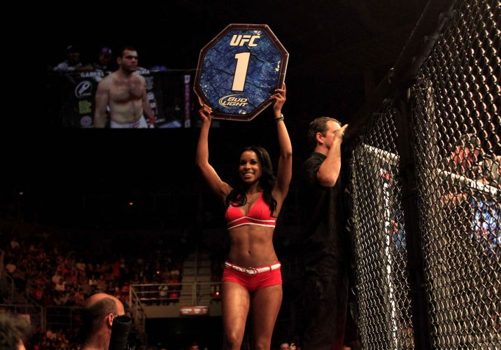 Ring girl desfila pelo octógono exibindo o cartaz do round e as belas formas