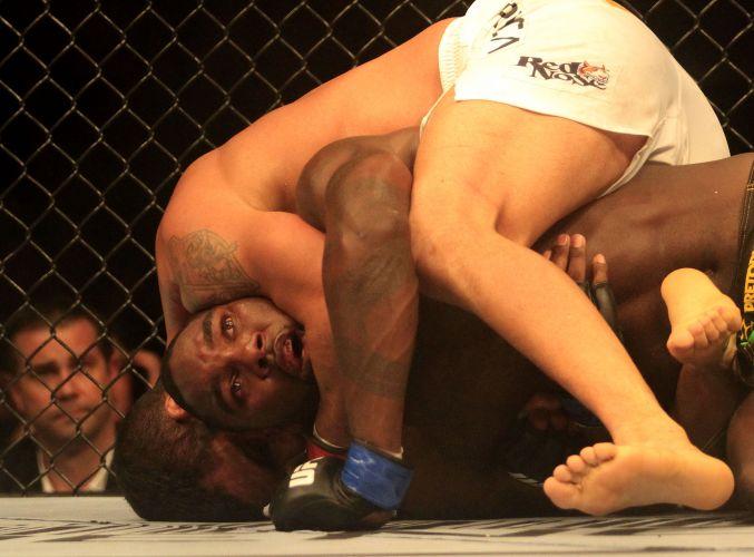 Anthony Johnson é agarrado por Vítor Belfort durante luta. Brasileiro venceu por submissão e levou torcida à loucura
