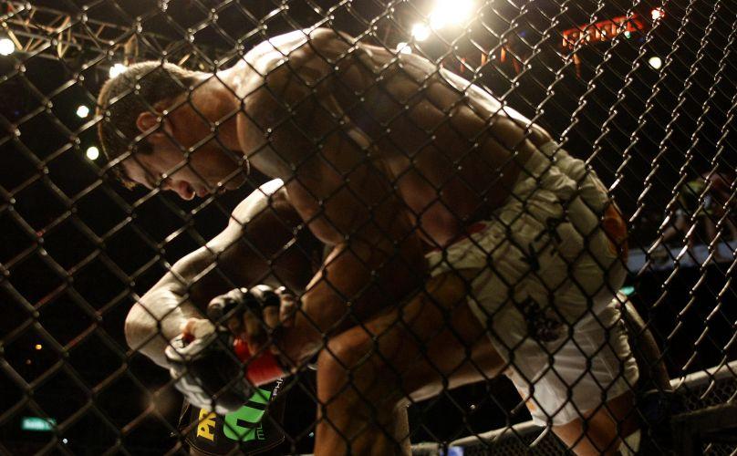 Vítor Belfort é pressionado contra as grades. Luta começou complicada para o brasileiro, que se recuperou e conseguiu a submissão para vencer no UFC 142