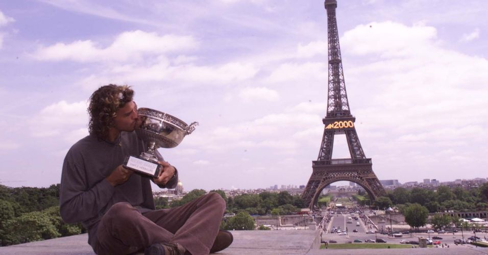 Gustavo Kuerten posa com o trofu de Roland Garros em frente  torre Eiffel, em Paris