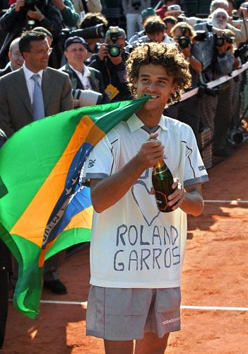 Guga comemora o ttulo de Roland Garros com uma garrafa de champanhe e usando camisa com uma declarao de amor ao Grand Slam francs aps o tricampeonato