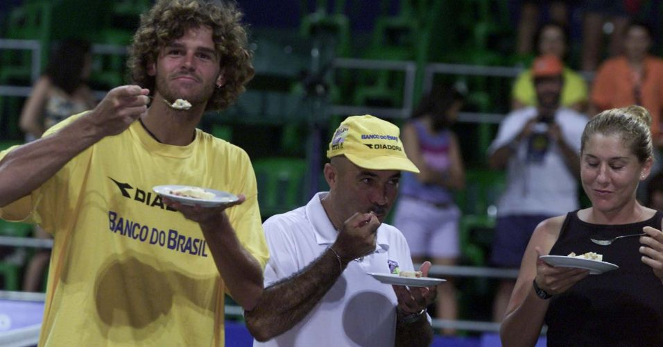 Antes de disputar o Aberto do Brasil na Costa do Sauipe, Gustavo Kuerten come bolo em comemorao de seu aniversrio ao lado do tcnico Larri Passos e da tenista Monica Seles