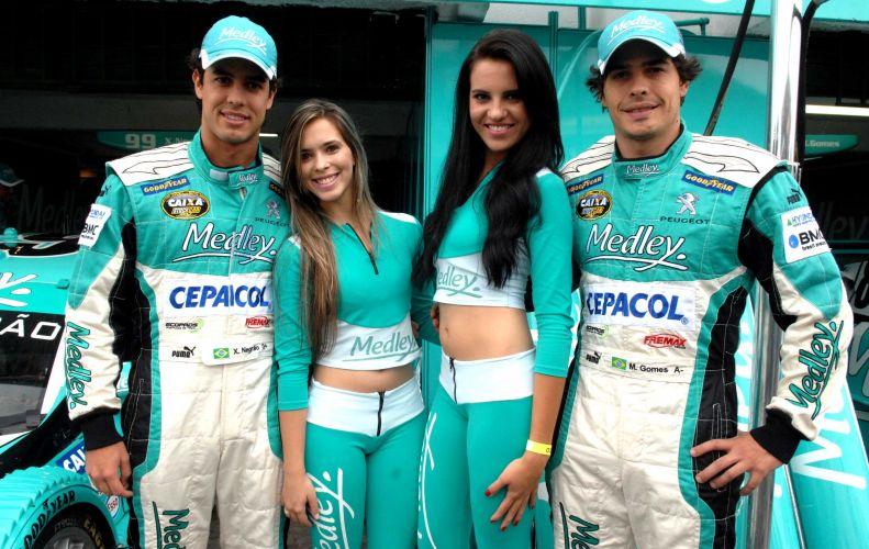 Pilotos Xandinho Negrão e Marcos Gomes posam para foto ao lado das 'grid girls'