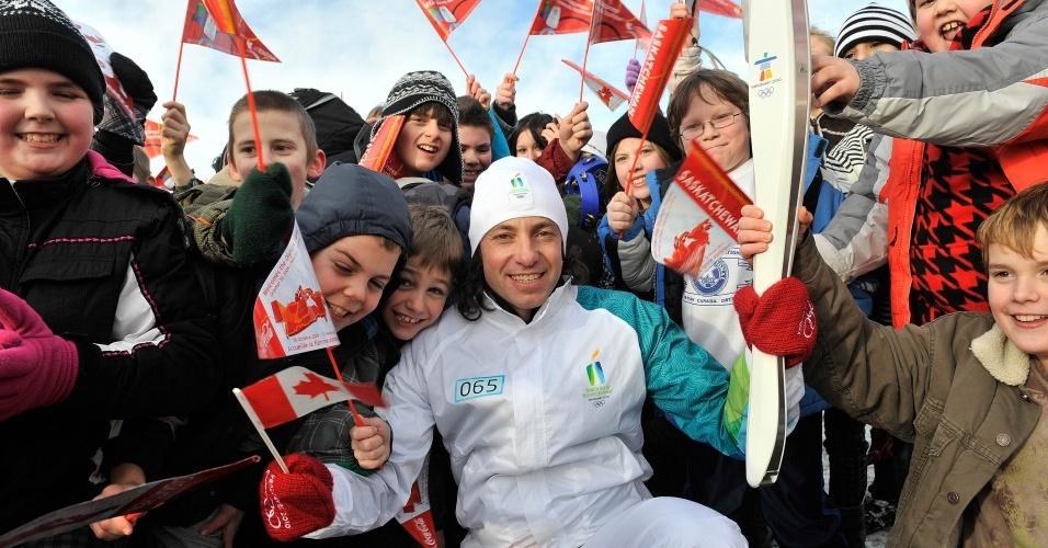 Philippe Candeloro, ex-campeão da patinação, posa com canadenses, segurando a tocha olímpica