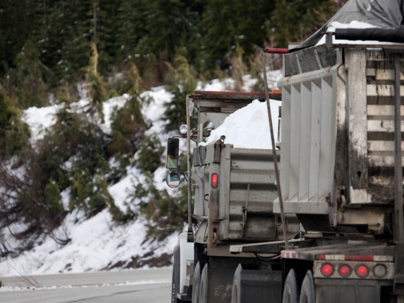 Caminhões levam neve para a montanha Cypress, que receberá provas durante os Jogos de Inverno, na próxima semana