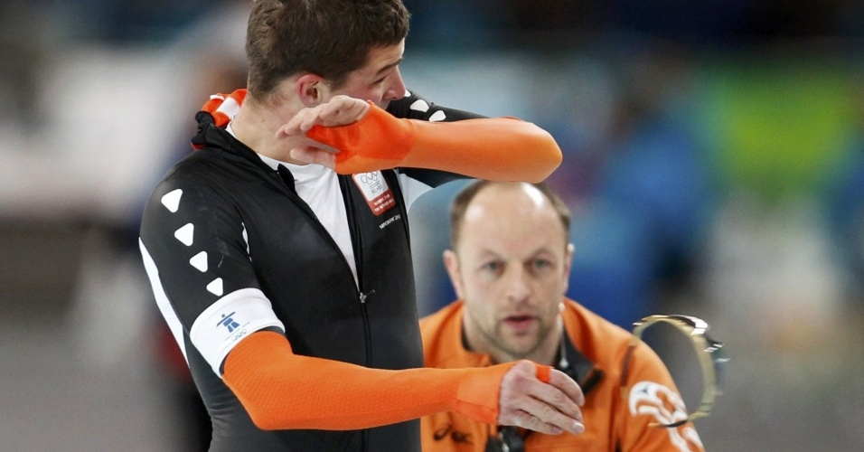 Holandês Sven Kramer é observado pelo técnico enquanto joga no chão seus óculos; ele foi desqualificado dos 10.000 m na patinação de velocidade