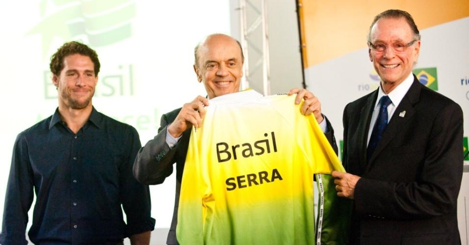 Ao lado do judoca Flávio Canto (e), o candidato à Presidência da República José Serra recebe um uniforme da delegação brasileira olímpica das mãos do presidente do COB, Carlos Arthur Nuzman