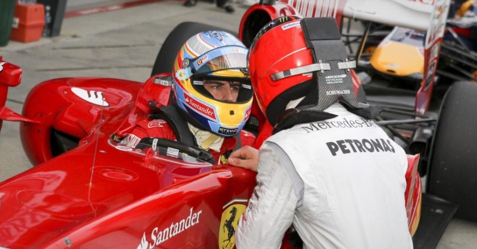 Michael Schumacher vai ao carro de Fernando Alonso para reclamar que o espanhol atrapalhou sua volta em treino