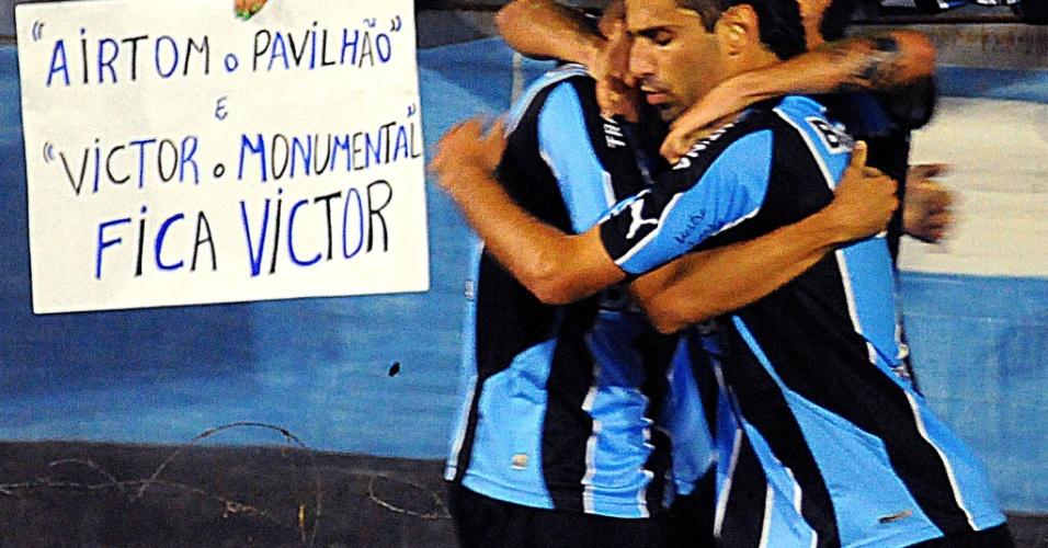 Jogadores do Grêmio comemoram ao lado de um cartaz pedindo pela permanência de Victor