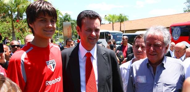 Prefeito Gilberto Kassab e presidente Juvenal Juvêncio posam com criança no CT de Cotia, em São Paulo