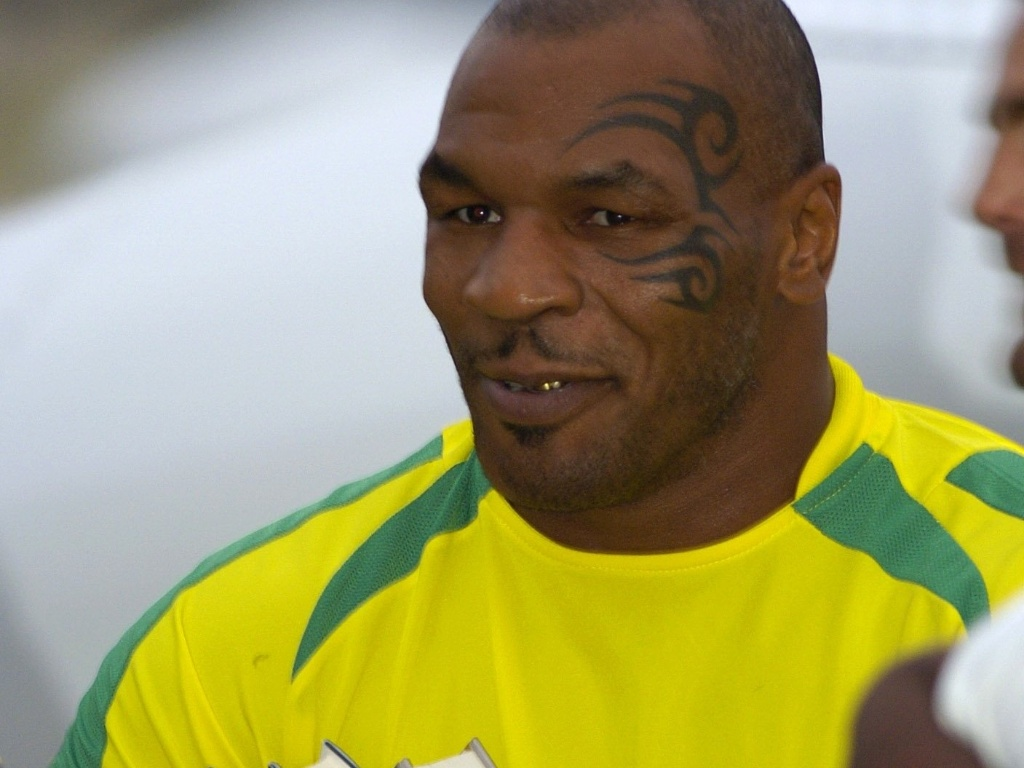 Mike Tyson, com a camiseta da seleo brasileira, carrega livros sobre pombos; ele ganhou reality show em que colocar as aves em corridas