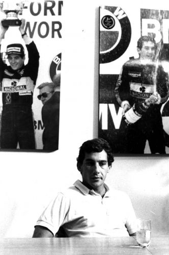 Senna com quadros ao fundo que ressaltam as suas conquistas na Lotus