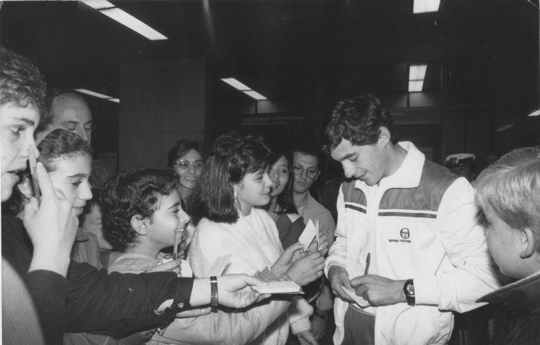 Piloto brasileiro dá autógrafos cercado por fãs em 1986