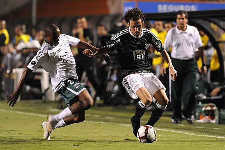 Palmeirense Lincoln (d) tenta passar pela marcação de Carlos Alberto, do Goiás, em duelo no Pacaembu; time esmeraldino vence de virada e está na final da Sul-Americana