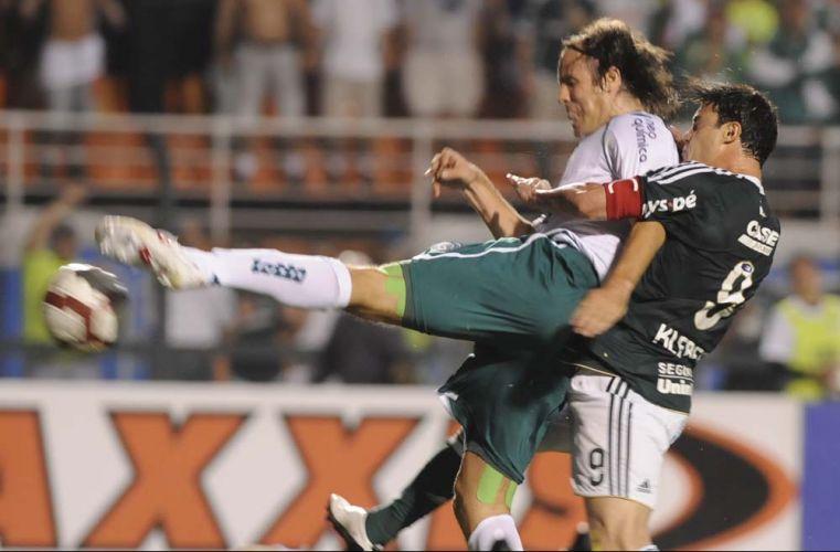 Ex-jogador do Palmeiras, zagueiro Marcão (e), do Goiás, isola a bola em disputa dura de bola com o atacante palmeirense Kleber na partida de volta da semifinal; time esmeraldino vence de virada e está na final