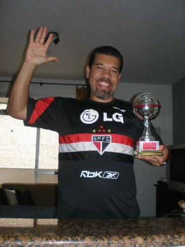 Ari veste camisa do goleiro e segura trofeu do filho, que foi artilheiro de um torneio na Itália