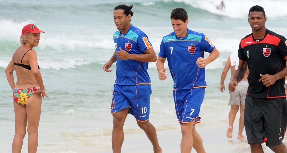 Ronaldinho Gaúcho, Thiago Neves e Felipe se exercitam na areia enquanto são observados por torcedores