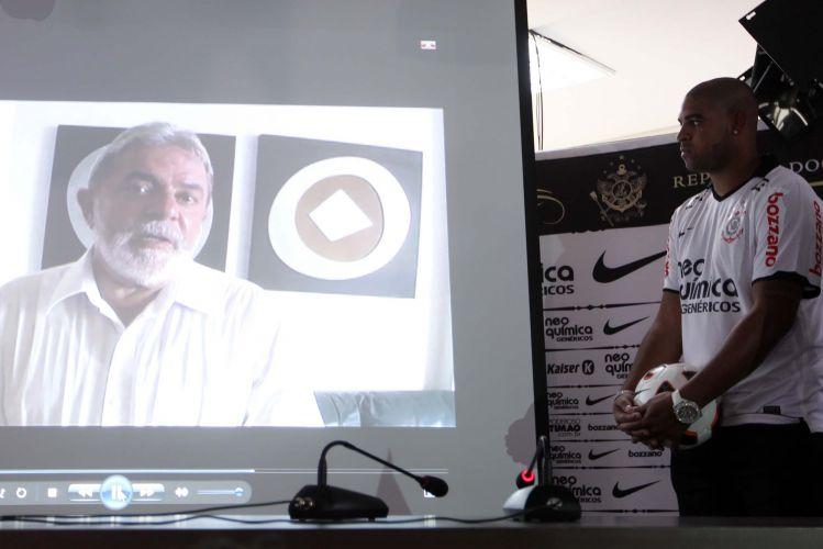 Adriano observa o vídeo gravado pelo ex-presidente Lula, exibido pouco antes da sua entrevista coletiva. Na gravação, o político deseja sorte ao novo corintiano e parabeniza a contratação feita por Andrés Sanchez.