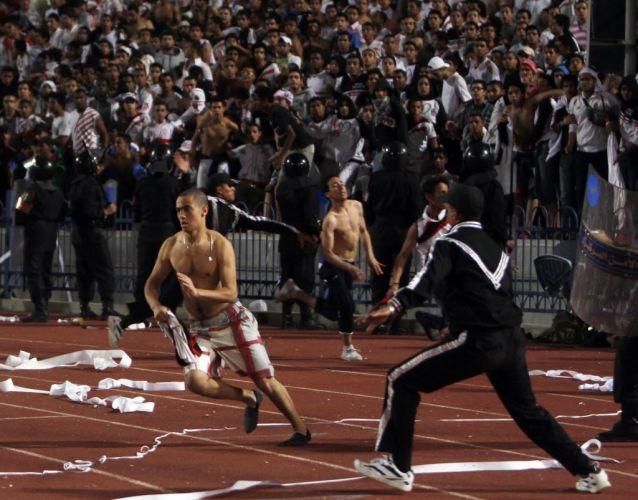 Um torcedor do Zamalek corre pelo gramado. Ele faz parte da multidão que invadiu o campo para agredir o árbitro após a eliminação de seu time
