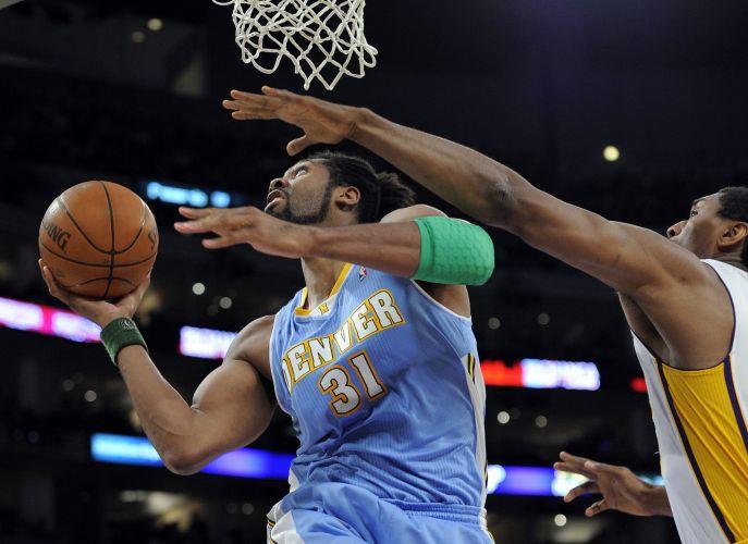 Pivô brasileiro Nenê tenta o arremesso marcado por Ron Artest, dos Lakers. O Denver Nuggets conseguiu vencer o time de Los Angeles, na casa dos rivais, por 95 a 90. Nenê anotou 12 pontos e pegou sete rebotes, enquanto o rival Kobe Bryant teve 28 pontos, mas não conseguiu segurar os visitantes