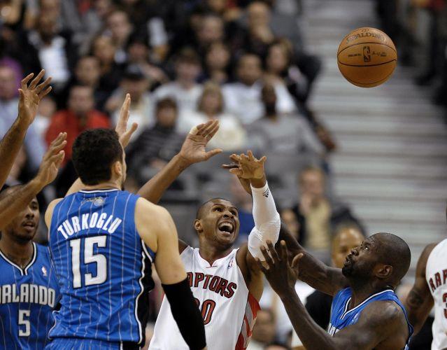 Leandrinho perde a posse da bola diante da defesa do Orlando Magic. Toronto Raptors, contudo, venceu a partida