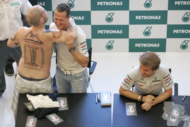 Nico Rosberg (d), companheiro de Michael Schumacher na Mercedes, diverte-se ao ver seu compatriota ser abraçado por fã, que homenageou o ídolo com várias tatuagens pelo corpo