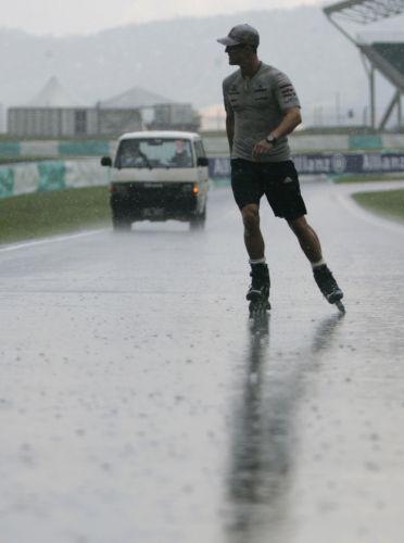 Michael Schumacher passeia com patins pela pista de Sepang na chuva antes dos treinos livres para o Grande Prêmio da Malásia