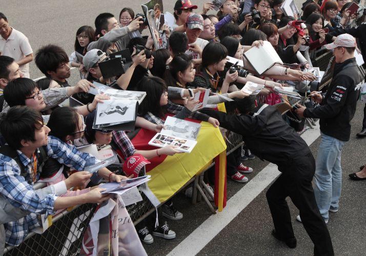 Dezenas de fãs se aglomeram para conseguir um autógrafo de Michael Schumacher, piloto da Mercedes, em Xangai