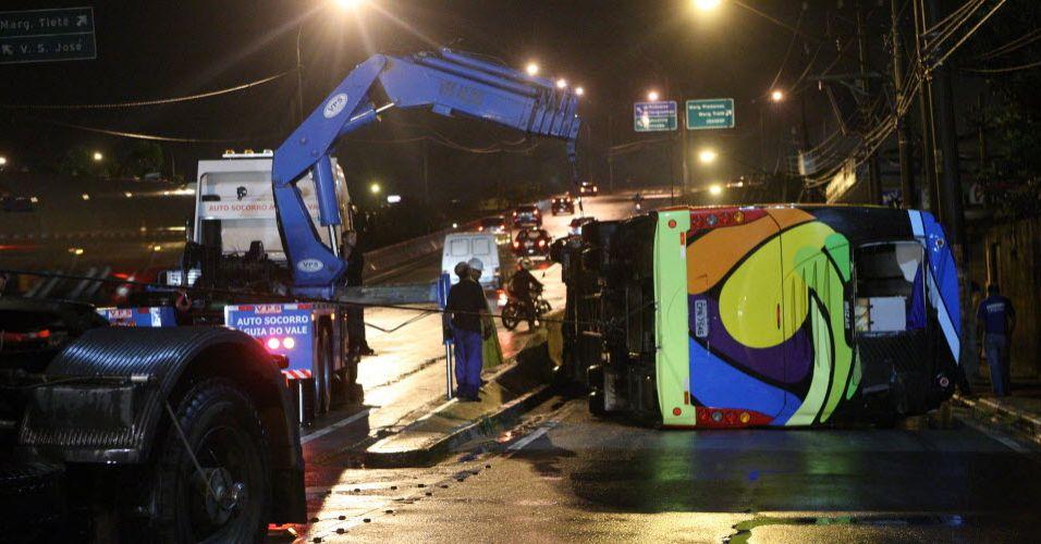 Homens trabalham para desvirar ônibus da delegação do Vôlei Futuro, que sofreu um acidente antes do jogo contra o Sollys/Osasco na Superliga feminina de vôlei
